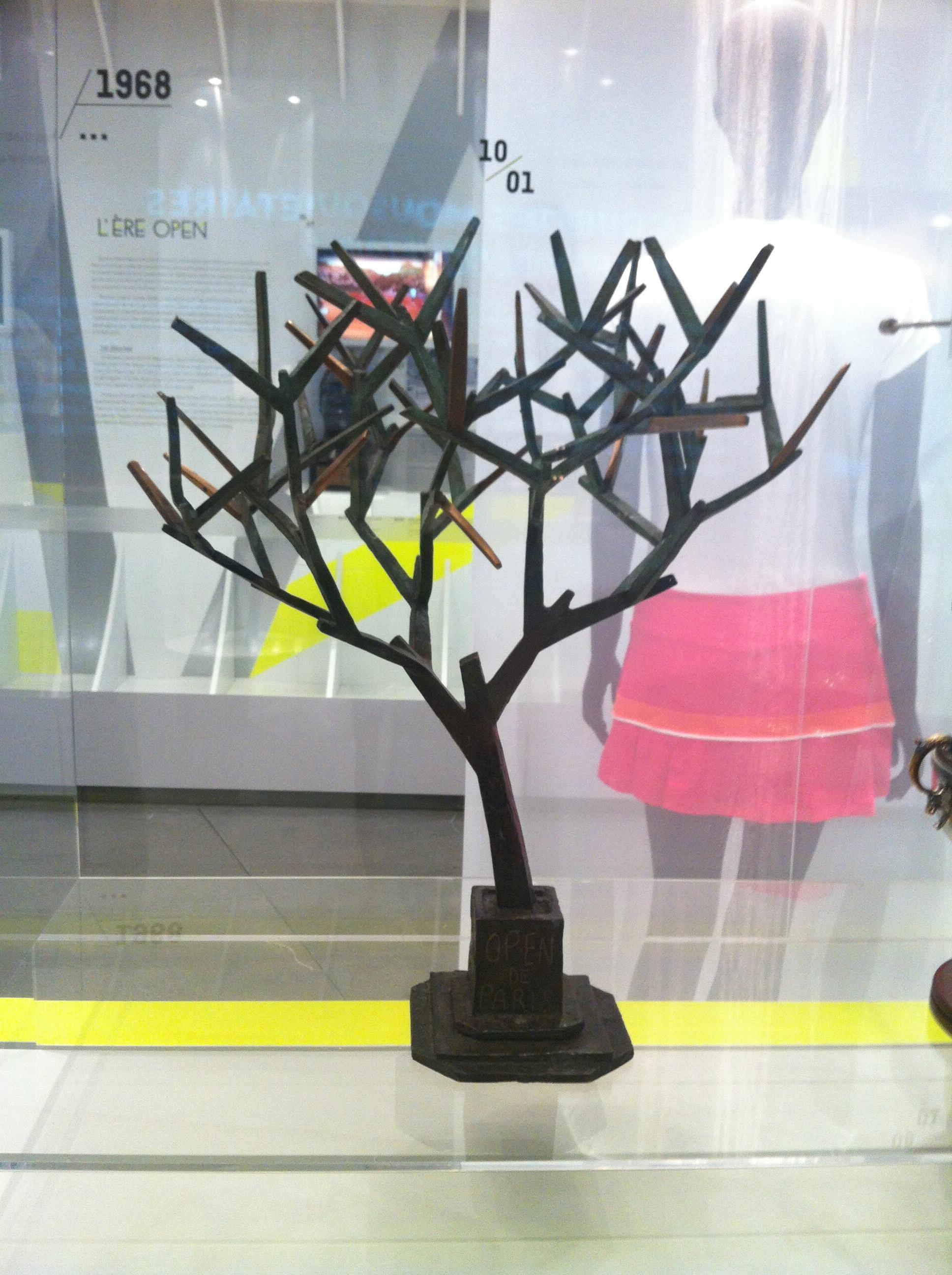 Retournant un tableau de progression des Internationaux de France, l'artiste italien Lucio Fanti voit se dessiner la silhouette d'un arbre. Sur cette inspiration, il réalise ce trophée original en bronze, unique au monde, et remis au vainqueur de l'Open de Paris de 1991 à 2006 (sic).