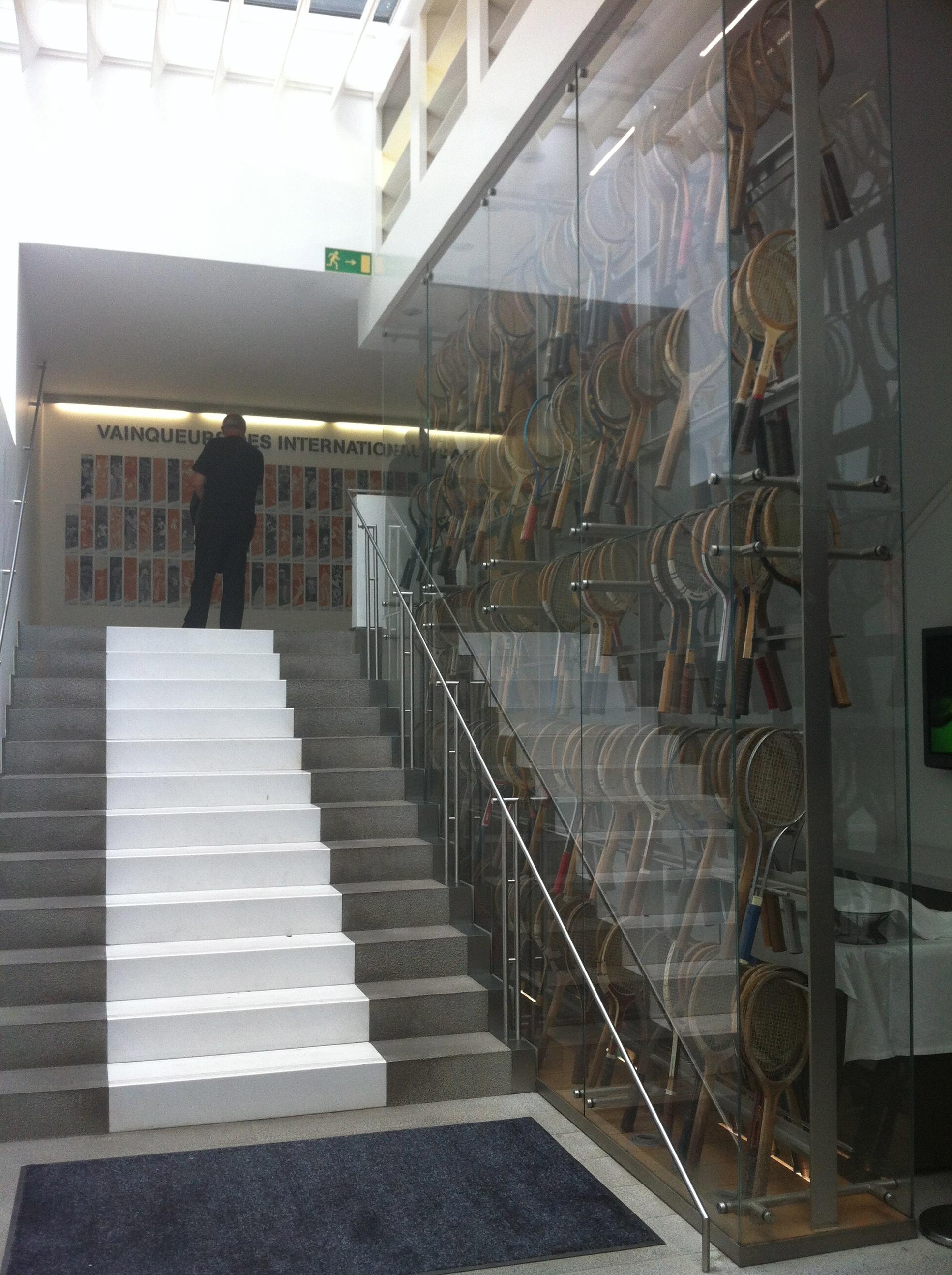 À droite, une vitrine de raquettes ; en haut, une mosaïque de photos réunissant tous les champions couronnés à Roland Garros.